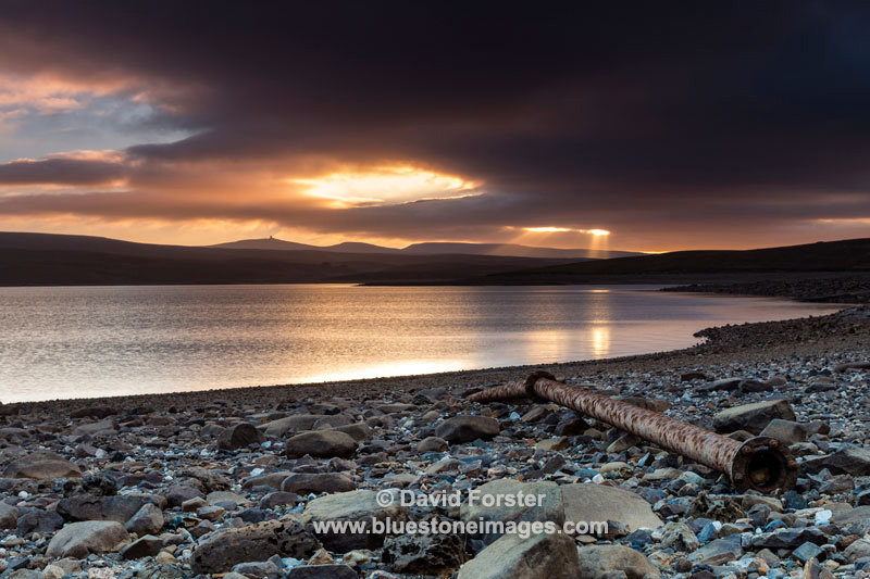 A spectacular sunset over Cow Green reservoir with Cross Fell and the Dun Fells illuminated by crepuscular rays, Upper Teesdale, County Durham, UK