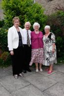 A happy couple celebrating their 50th Wedding Anniversary with their two bridesmaids