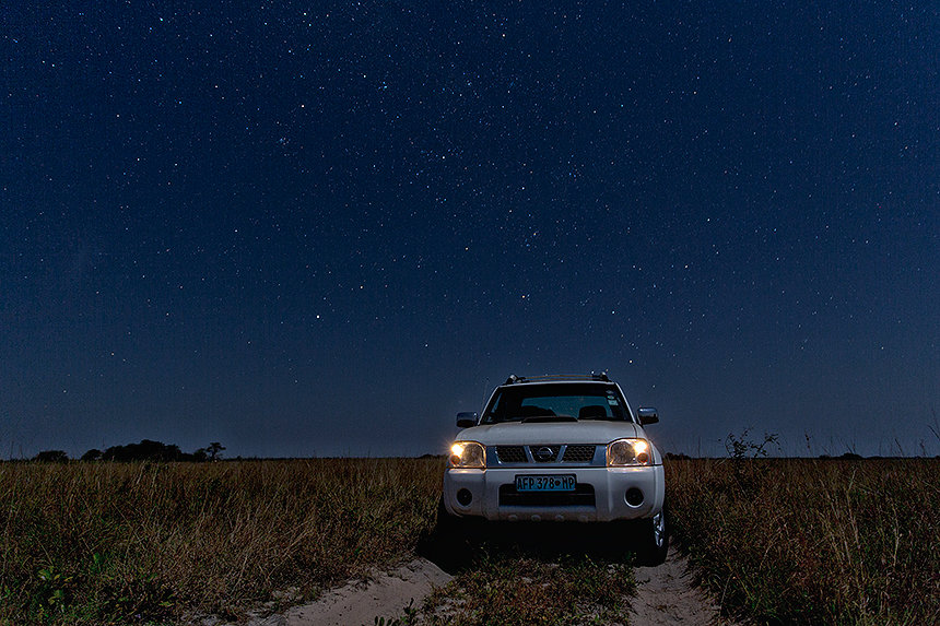 Our 4x4 under a starry night sky in the grasslands of Maputo Special Reserve.