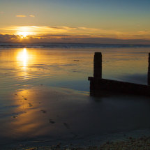 Sunset over beach and breakwater.