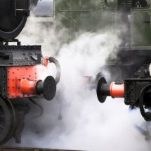 Close up of steam emitting between locomotives
