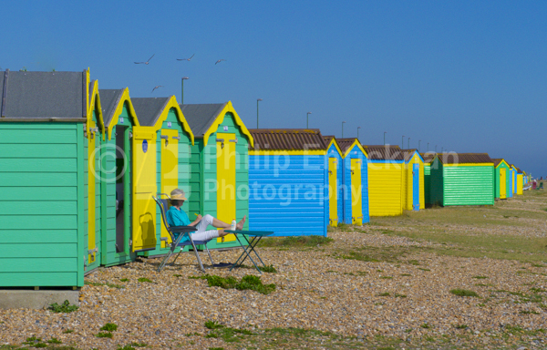 Woman sitting by beach huts, Littlehampton ,England