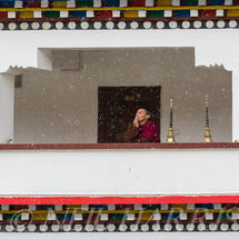 Monk on balcony in snow