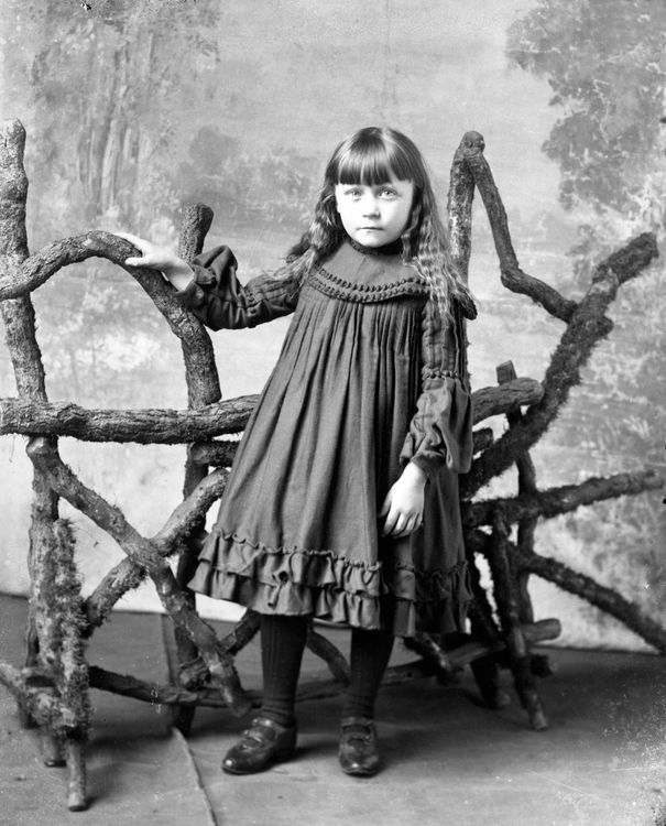 Portrait of a girl with a rustic bench c.1903