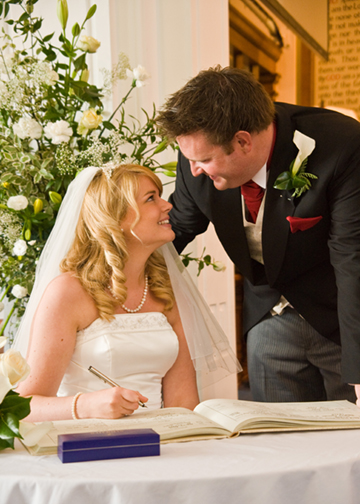 The happy couple sign the register