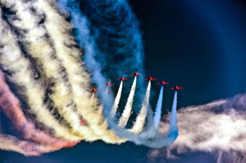 Red Arrows against a dark blue sky.