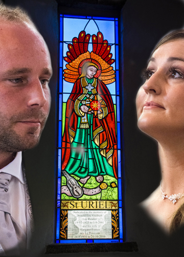 Tracey&James beside a stained glass window