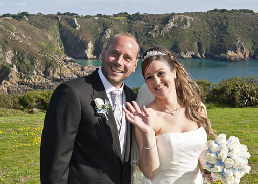 Waving to their guests in front of a stunning clifftop backdrop.