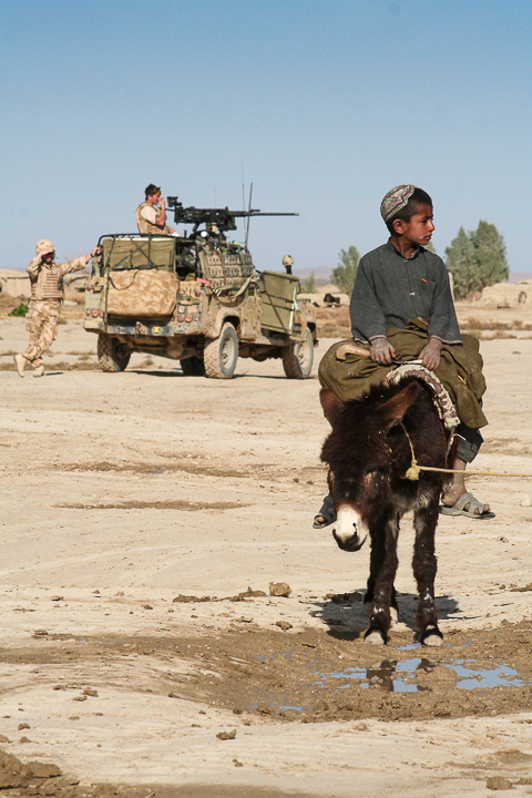 An Afghan boy watches a British patrol. Helmand Province, Afghanistan