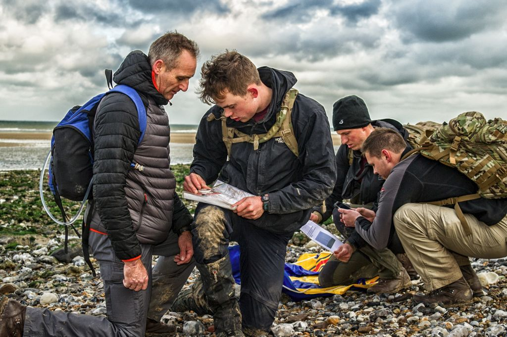 Participants in a navigation exercise check their position on a windswept French beach.