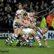 Hull FC pile on the pressure in a tackle against Wigan at the KC Stadium, Hull