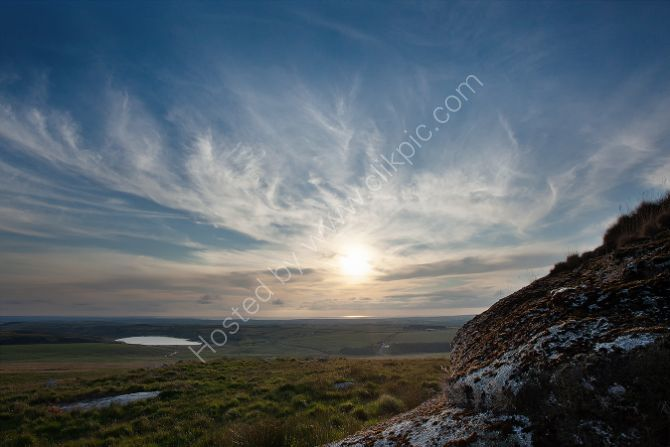 Sun setting over Camelford  from Rough Tor Bodmin Moor Cornwall