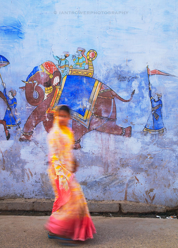 Woman walking past mural, Bundi, Rajasthan, India