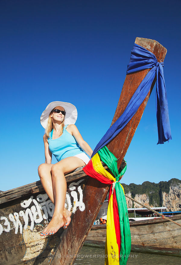 Woman sitting on boat on Railay beach, Thailand