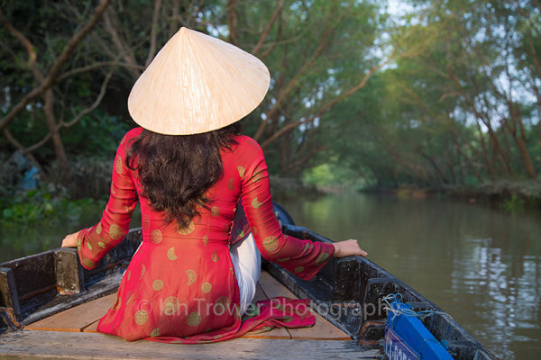 Woman wearing ao dai dress on canal, Can Tho, Vietnam