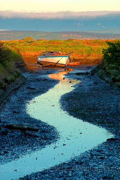 Lone yacht at low tide on Penngton Marsh, Lymington, Hampshire, England