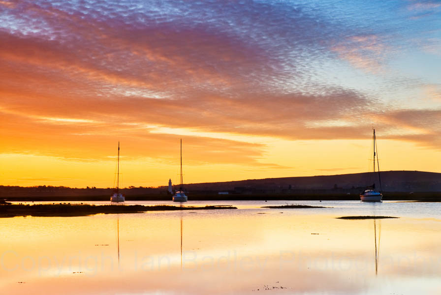 Dawn over the Isle of Wight reflected in the water off Keyhaven with moored yachts, Hampshire, England