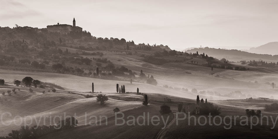 Cypress trees over rolling hills below Pienza, Tuscany, Italy