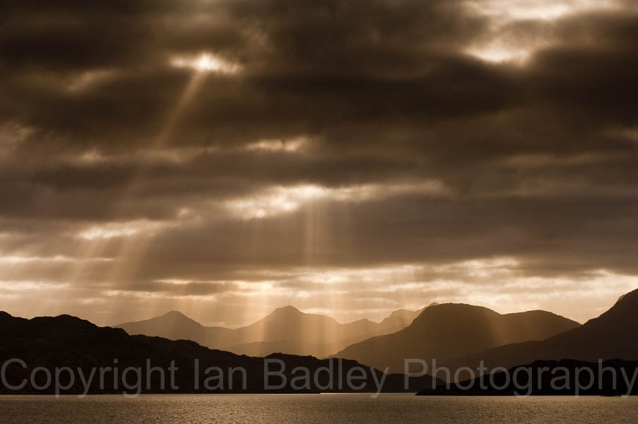 Sun light though the storm clouds over highland mountains, Scotland