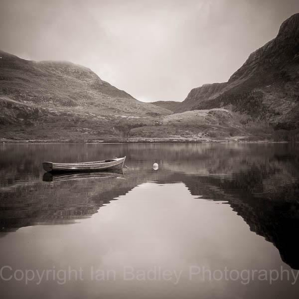 Moored boat on a still Loch Marie, Scotland