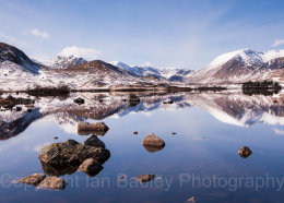 Still loch and rocks at first light over snow covered mountains, Rannoch moor, scotland
