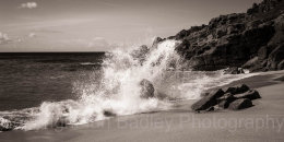 Waves crashing on rocks and a sandy beach, Cornwall, England