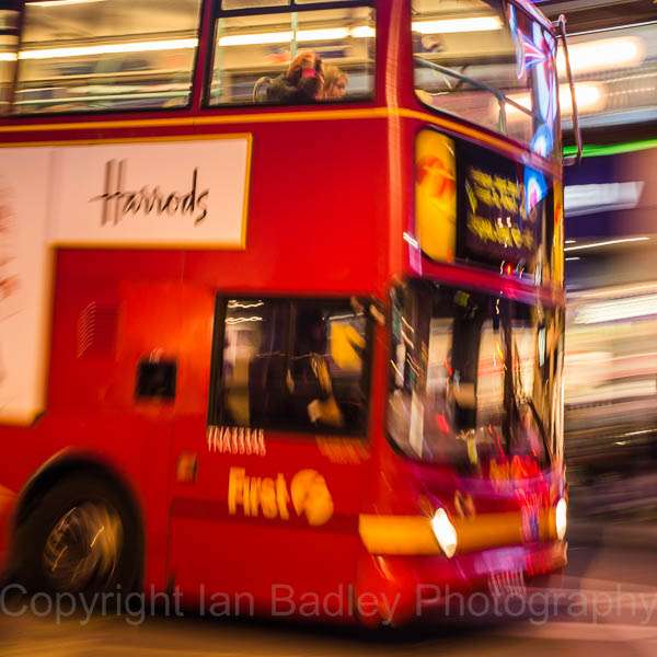 Red London bus moving at night
