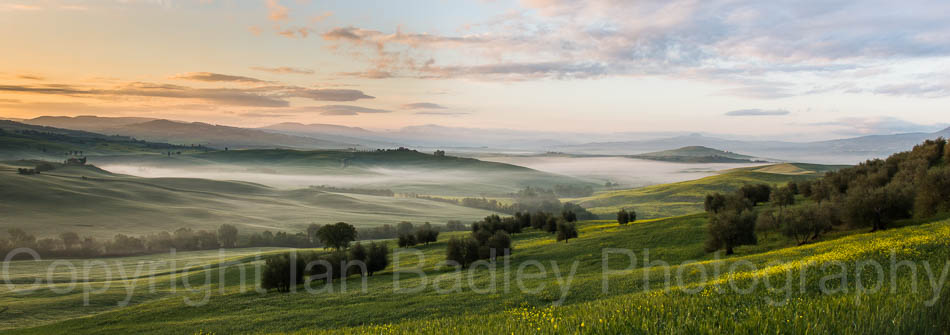 Green grass and sunrise over the UNESCO Val d'Orcia, Italy