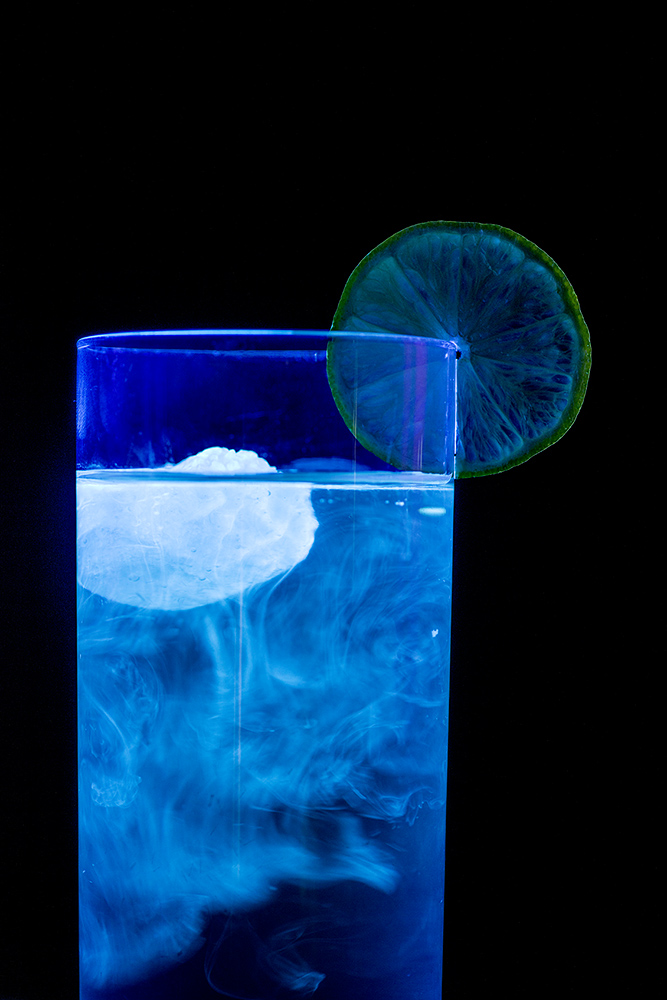 Tonic water fluorescing in UV radiation.