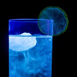 Tonic water fluorescing in UV radiation.