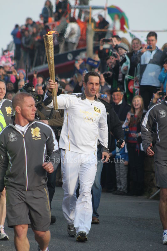 Ben Ainslie with the Olympic Torch at Land's End