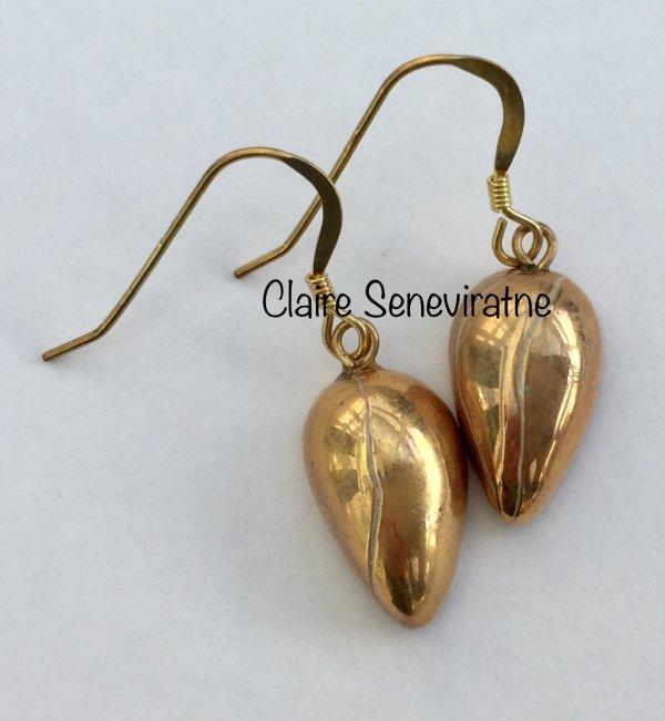 Small gold teardrop earrings.