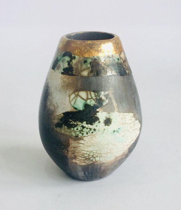 Small upright smoke-fired ceramic pot.