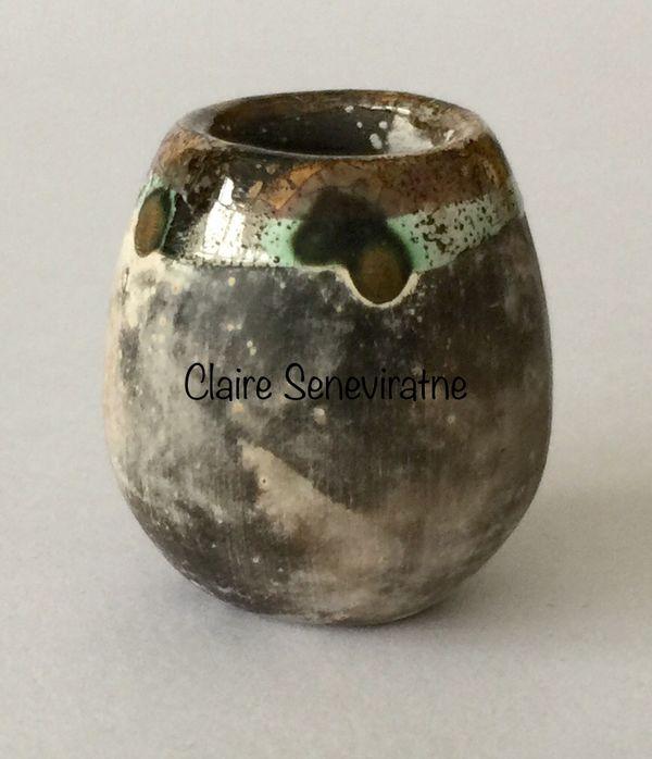 Tiny upright smoke fired pot.