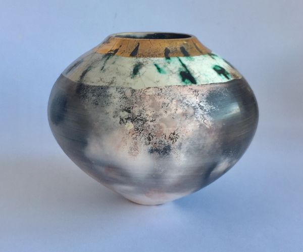 Round smoke-fired pot with glaze and gold lustre.