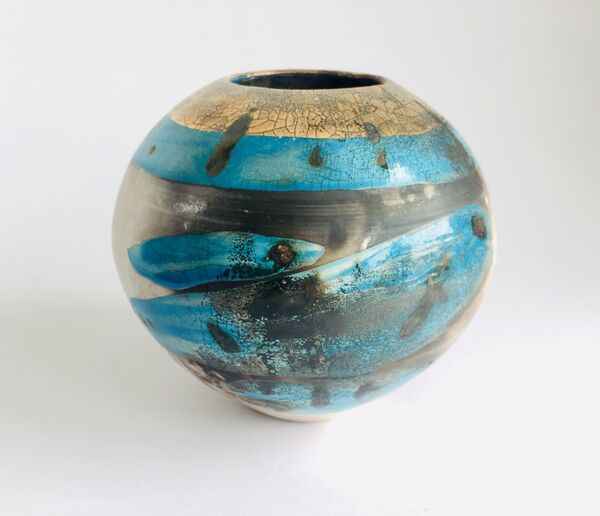 Blue smoke-fired ceramic pot with glaze and gold lustre.