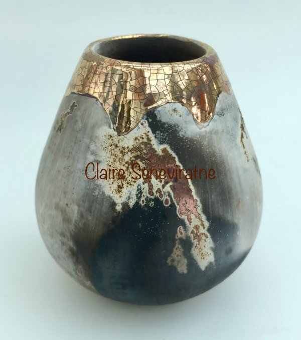 Small ceramic smoke fired pot with gold and copper.