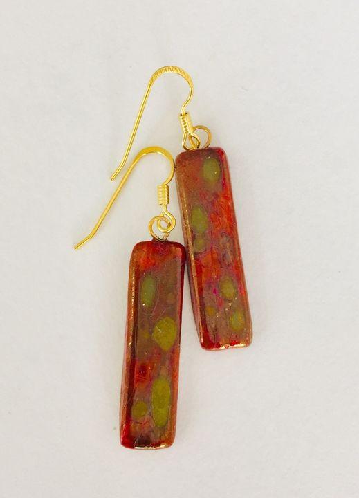 Red rectangular ceramic earrings with matt gold patterns.