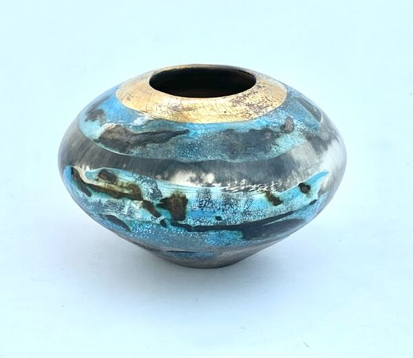 Blue and gold pit-fired vessel.