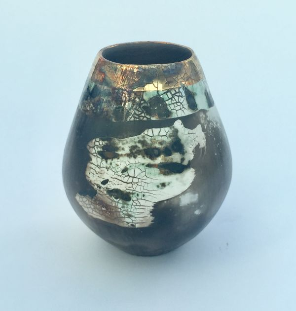 Sawdust fired ceramic pot with partial glaze and gold lustre.