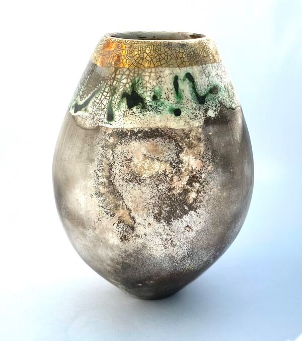 Smoke-fired pot with gold lustre and copper carbonate markings.