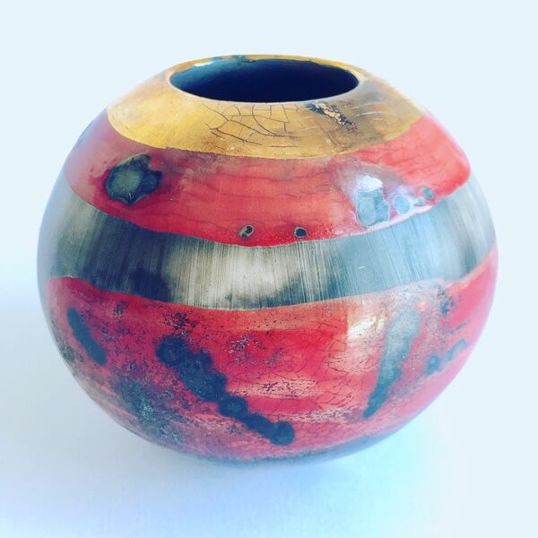 Small red smoke-fired porcelain vessel.