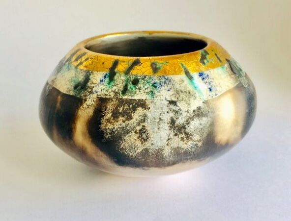 Burnished smoke-fired ceramic pot with gold lustre.