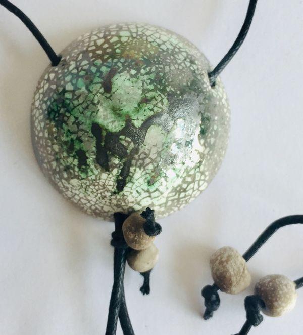 Round raku pendant with greens,greys and white.
