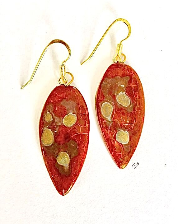 Red leaf shaped ceramic drop earrings with matt gold patterns.