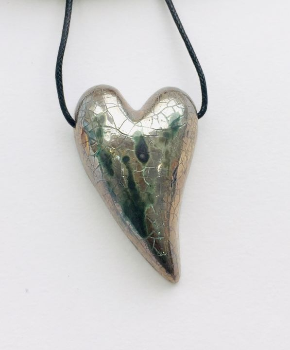 Silver heart ceramic pendant with textured markings.