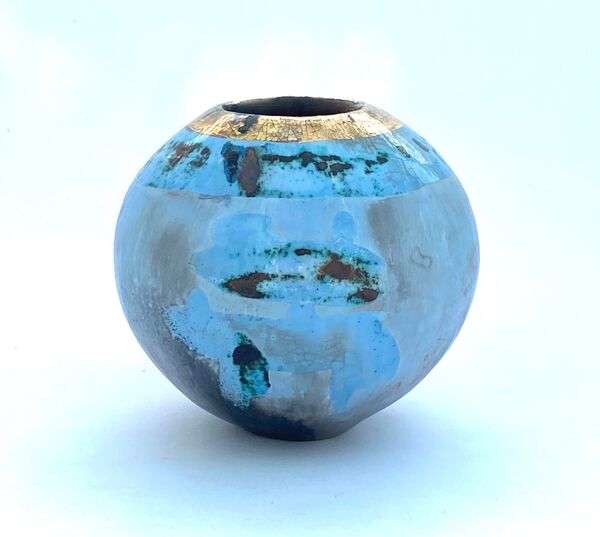 Small round blue smoke-fired ceramic pot with gold lustre.