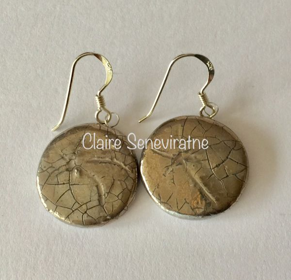 Round ceramic earrings with silver lustre.