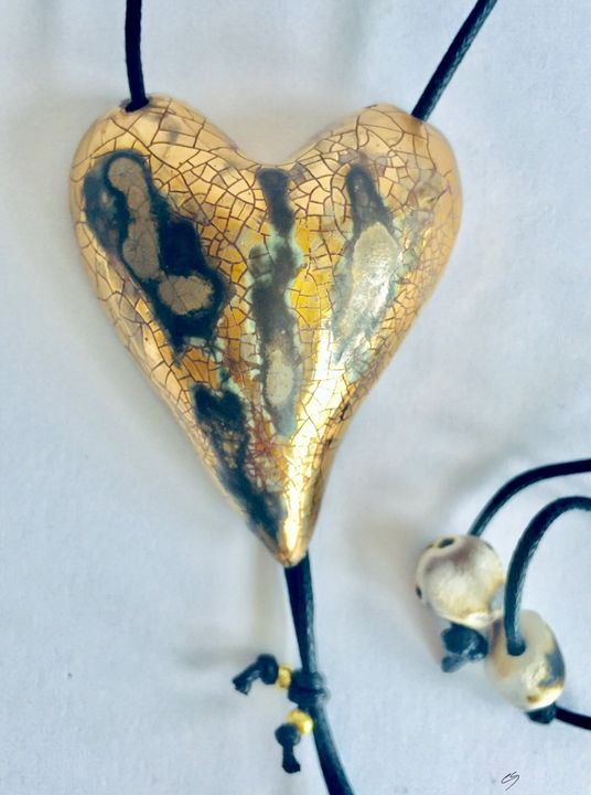 Large gold heart pendant with crackled textures.