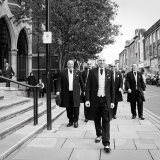 The groom and his groomsmen walking to the Guildhall